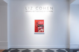 Artwork by Liz Cohen hung on gallery wall underneath sign that states artist's name. Artwork shows a magazine cover and a red high heeled shoe on a red background. Hung on white wall.
