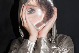 Photograph by Corine Vermeulen of a woman in silver raincoat holding clear water balloon over face against black background