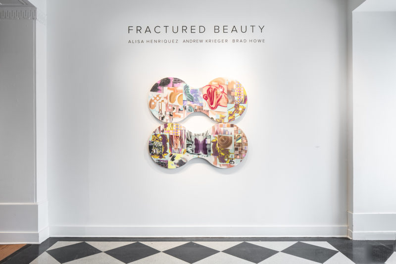 Photo of Alisa Henriquez painting below title of Fractured Beauty on the wall