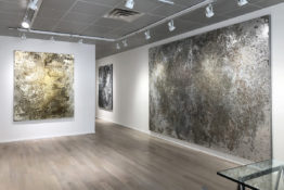 Installation view of Rosalind Tallmadge show. Three large, gold and silver metallic paintings hanging on gallery wall