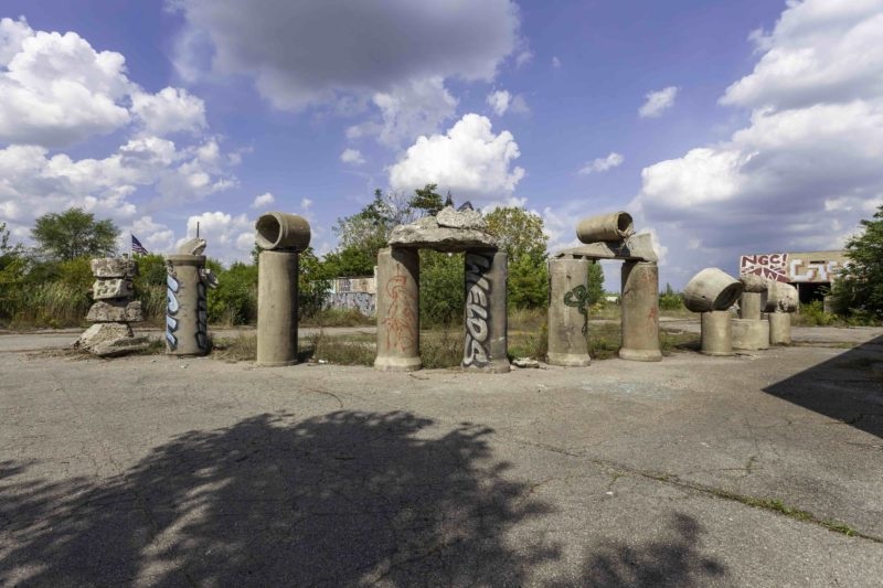 Photograph by Scott Hocking of eight sculptures made of repurposed concrete pipes. Lined up on pavement in front of trees. Blue sky with clouds.